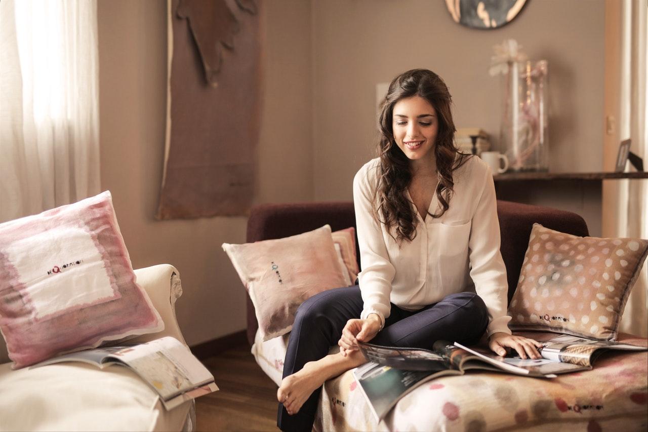 Kvinne mellom duse sofaputer
